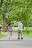 Couple having fun in Central Park in New York City. Couple walking and dancing on path in Central park in New York City royalty free stock image