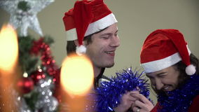 Couple having fun at Christmas time with decorated tree and lights stock video