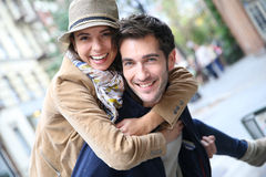 Couple having fun in the city streets. Man giving piggyback ride to girlfriend, having fun Stock Image