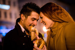 Couple having fun - eating together in street Stock Image