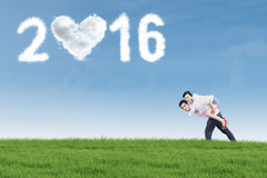Couple having fun at field with numbers 2016 Stock Photography