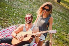 Couple having fun with guitar on a picnic. Sexy couple having fun with guitar and laughing on a picnic Stock Photos