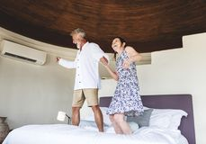 Couple having fun jumping on the bed stock image