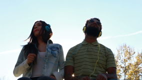 Couple having fun listening to music with headphones on sunny day. Low angle view of young couple having fun listening to music with headphones on beautiful stock video footage