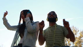 Couple having fun listening to music with headphones on sunny day. Low angle view of young couple having fun listening to music with headphones on beautiful stock video