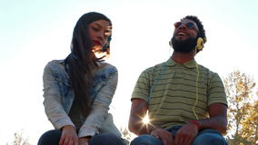 Couple having fun listening to music with headphones on sunny day. Low angle view of young couple having fun listening to music with headphones on beautiful stock footage
