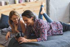 Couple having fun looking at photos on a pro photo camera Stock Image
