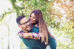 Couple having fun man giving piggyback to woman Stock Image