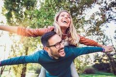 Couple having fun man giving piggyback to woman in park Royalty Free Stock Image