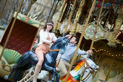Couple having fun on merry-go-round Stock Photo