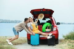 Couple having fun near car trunk with suitcases stock image
