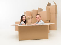 Couple having fun in new home. Couple sitting in a box, having fun after moving in new home stock photos