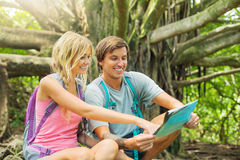 Couple having fun outdoors on hike. Attractive young couple having fun together outdoors on hike looking at map Stock Images