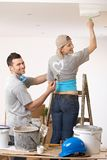 Couple having fun at painting. Smiling woman painting the ceiling standing on ladder, laughing guy painting heart on tshirt Stock Photos