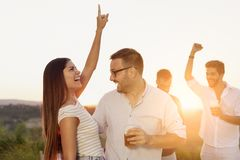 Couple having fun at a party. Couple in love having fun at an outdoor summertime party, dancing and drinking beer stock images