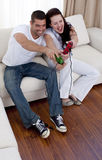 Couple having fun playing video games. Smiling couple having fun playing video games in living-room Stock Photo