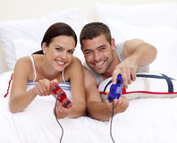 Couple having fun playing videogames in bed Stock Images
