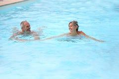 Couple having fun in pool. Active senior couple in resort pool Stock Photography