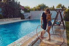 Couple having fun pour each other with garden hose Stock Image