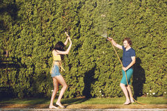 Couple having fun pour each other with garden hose Stock Images