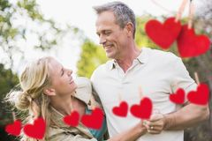 Couple having fun with red hanging hearts Stock Images