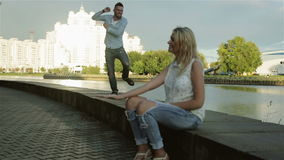 A couple having fun at the river side. The man is dancing on the woman's hand. Than she is fed up and walks away. He runs after her stock video footage