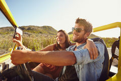Couple having fun on road trip. Man driving car with women taking selfie on her smart phone. Couple having fun on road trip on a summer day Stock Photography
