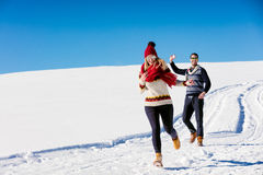 Couple having fun running down slope Royalty Free Stock Photo