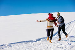 Couple having fun running down slope Royalty Free Stock Image