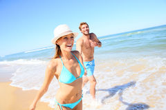 Couple having fun running by the sea Stock Photos