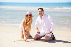 Couple having fun with the sand. Pretty young women drawing a heart and initials on the sand with her boyfriend at the beach and smiling Stock Photos
