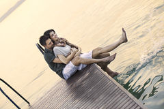 Couple having fun seated on a boardwak with a beautifull lake view Stock Photos