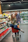 Couple having fun with the shopping cart in the supermarket. Cheerful couple having fun with the shopping cart while choosing food in the supermarket Royalty Free Stock Image