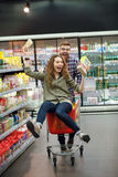 Couple having fun with the shopping cart in the supermarket. Happy young couple having fun with the shopping cart while choosing food in the supermarket Royalty Free Stock Photo
