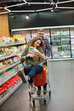 Couple having fun with the shopping cart in the supermarket. Happy young couple having fun with the shopping cart while choosing food in the supermarket Royalty Free Stock Photos