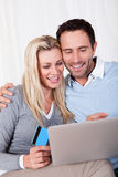 Couple having fun shopping online Royalty Free Stock Photos