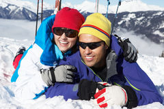 Couple Having Fun On Ski Holiday In Mountains. Laying In The Snow Stock Photo
