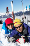 Couple Having Fun On Ski Holiday In Mountains. Laying In The Snow Stock Image