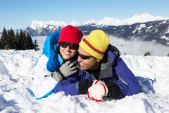 Couple Having Fun On Ski Holiday In Mountains. Laying In The Snow Royalty Free Stock Photography