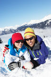 Couple Having Fun On Ski Holiday In Mountains. Laying In The Snow Stock Images