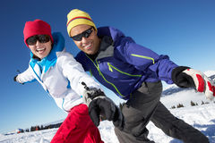 Couple Having Fun On Ski Holiday In Mountains. Posing For Camera Stock Images