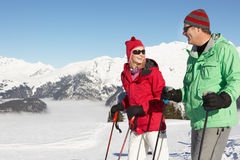 Couple Having Fun On Ski Holiday In Mountains. Smiling At Eachother Stock Photography