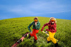 Couple having fun in ski suits with snowboards on the grass Royalty Free Stock Images