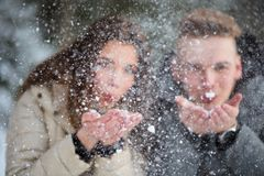 Young couple in love blowing snow away. Couple having fun on a snowy winter day Royalty Free Stock Photography