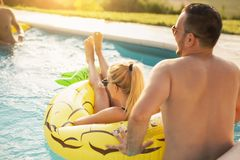 Couple having fun at a swimming pool. Couple in love at a poolside summer party, sunbathing and having fun; girl floating in the pool on a pineapple shaped air stock photo