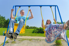 Couple having fun on the swing. Amorous couple on romantic date on swings outdoor. Love, relationship, family and people concept - smiling couple hugging in Stock Image