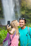Couple having fun taking pictures together outdoors on hike Royalty Free Stock Image