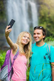 Couple having fun taking pictures together outdoors on hike stock photos