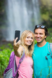 Couple having fun taking pictures together outdoors on hike royalty free stock photos