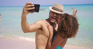 Couple having fun and taking selfie. Cheerful woman closing face of boyfriend with hat while standing on beach together and taking selfie stock video footage